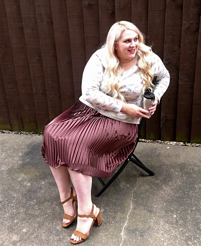 Me to enjoying family time in the garden, sat down hold cuppa, peahen jumper paired with satin brown pleated skiry for transitioning from summer to autumn