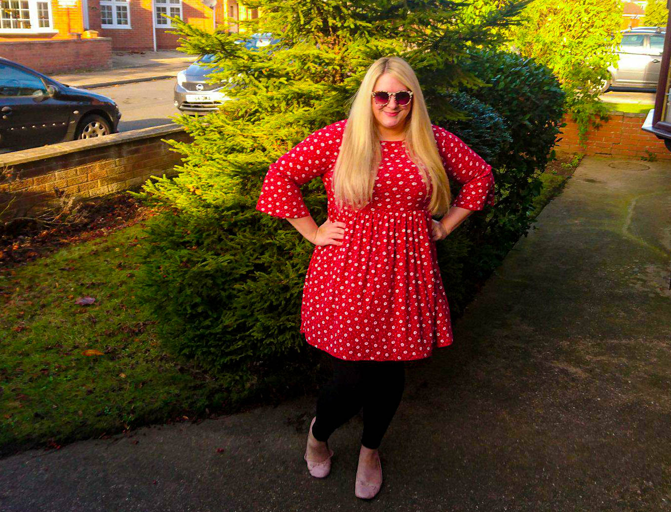Me standing in my front garden wearing a red dress from LOTD which finses above the knee. It has bell sleeves and an A-line fit