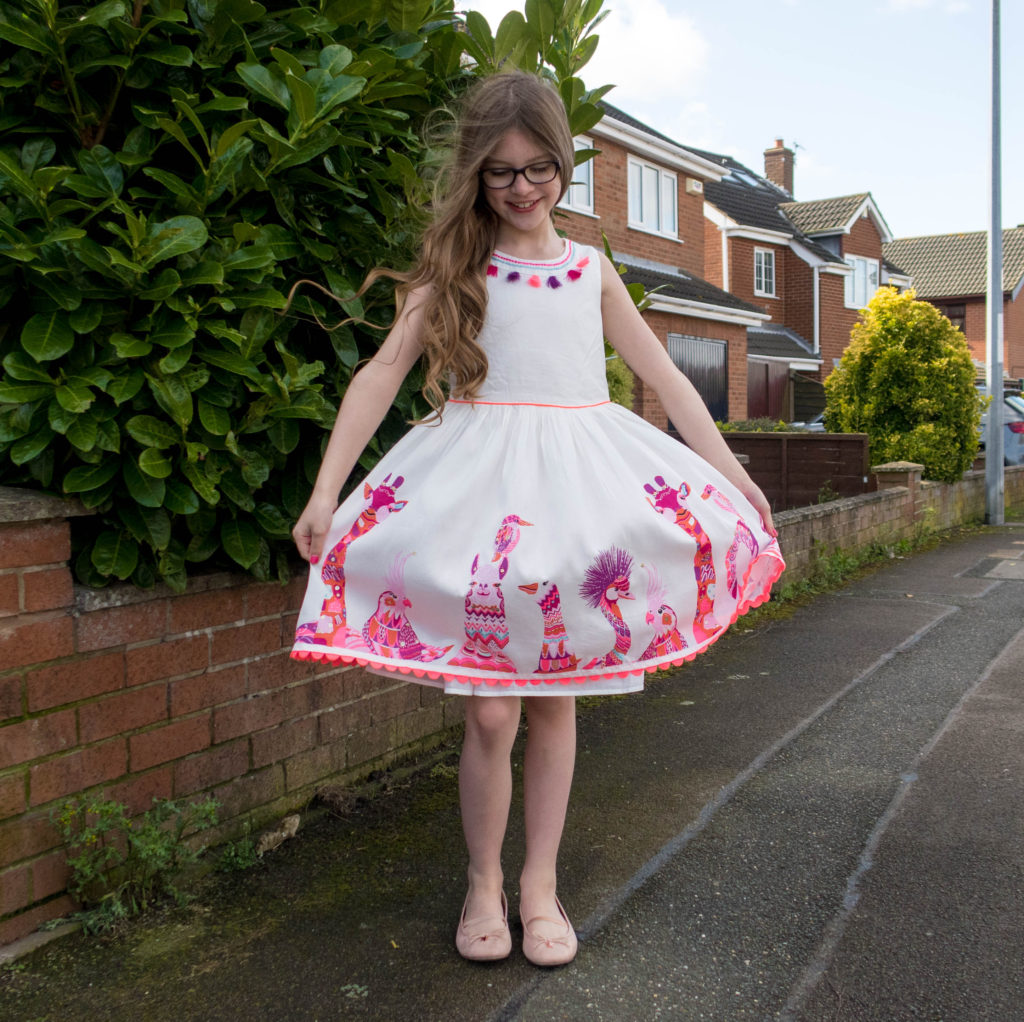 Emma wearing a Monsoons girls spring dresses in a whie design with pink animals and pink tassels around her neck. Emma is tall and thin and has long light brown curly hair, black glasses and is smiling