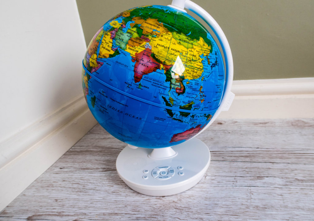 Oregon Scientific Smart Globe Myth, shown out of the box in daylight. Abrightly coloured glob with a white base and stand