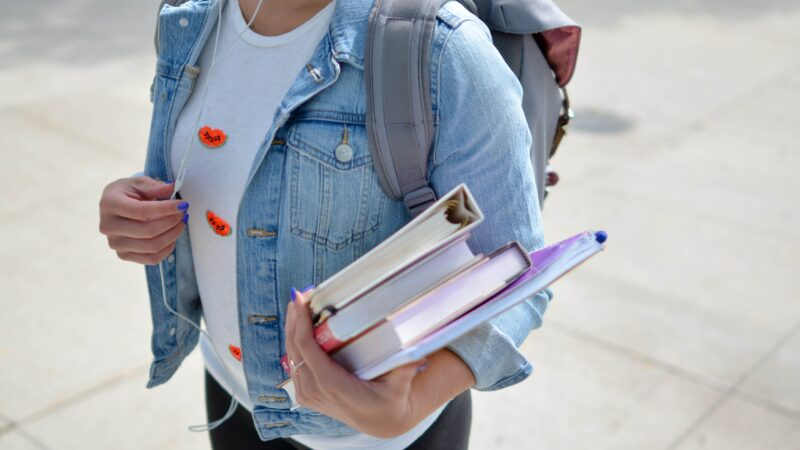 Girl's torso in denim jacket holding books, wearing a backpack. Why Post 16 Education is So Important