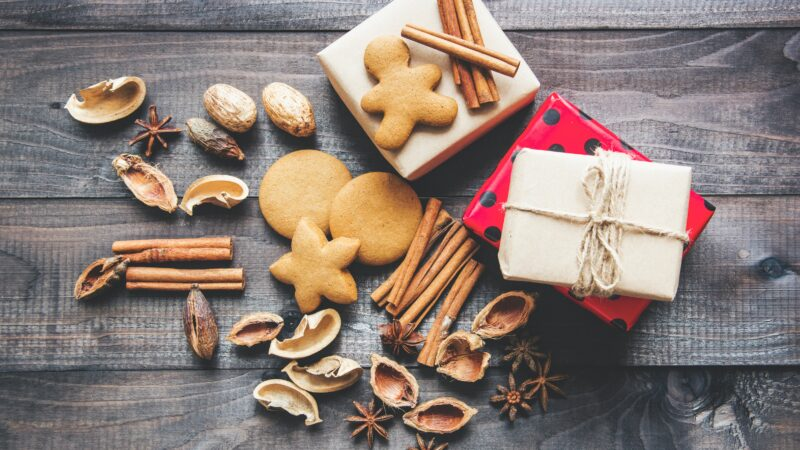 Pile of wrapped gifts, ginger bread men and other Christmas treats