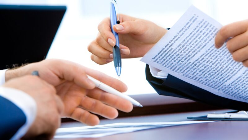 two hands holding documents and a pen